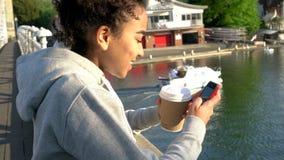 För afrikansk amerikanflicka för blandat lopp som kvinna för tonåring kvinnlig ung använder telefonen på en bro lager videofilmer