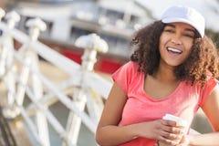 För afrikansk amerikantonåring för blandat lopp som kvinna dricker kaffe Royaltyfri Bild