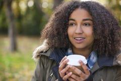 För afrikansk amerikantonåring för blandat lopp som kvinna dricker kaffe arkivfoto