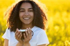 För afrikansk amerikantonåringen för det blandade loppet som kvinnan dricker kaffe, överträffar Arkivbild