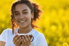 För afrikansk amerikantonåringen för det blandade loppet som kvinnan dricker kaffe, överträffar Arkivfoto