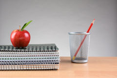 För Apple för lärareskrivbordanteckningsböcker kopp blyertspenna Royaltyfri Foto