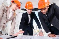 För arkitekter projekt därefter Arkitekt för tre businessmеn Arkivfoto