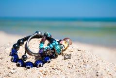 För armbandgarnering för tre kvinnlig lögn på sanden på en bakgrund av det blåa havet och blå himmel royaltyfri fotografi