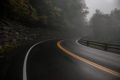 För asfaltväg för berg våt kurva på den regniga dagen för dimma royaltyfria bilder