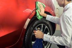 För asiatisk biltvätt kontroll- och rengörautrustning för man med den röda bilen för att göra ren till kvalitet till kunden på bi royaltyfri foto