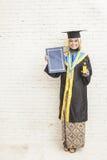 För avläggande av examenkappa för indonesisk kvinnlig doktorand bärande whil royaltyfri foto