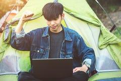 För bärbar datorkaffe för ung man campa tält arkivfoto