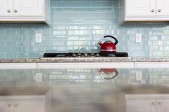 För backsplashgångtunnel för röd kokkärl glass kök för tegelplatta arkivbilder