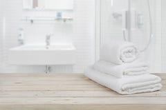 För bakgrunds- och vitbrunnsort för suddigt badrum inre handdukar på trä Arkivbild