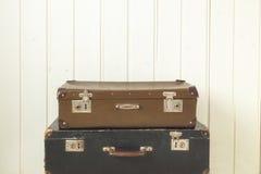 För bakgrundstappning för två gamla retro resväskor vitt trätona arkivbilder