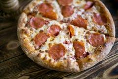 för banapeperoni för clipping bild isolerad pizza På en träbrun bakgrund Arkivfoto