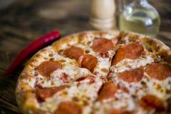 för banapeperoni för clipping bild isolerad pizza På en träbrun bakgrund Arkivbild