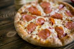 för banapeperoni för clipping bild isolerad pizza På en träbrun bakgrund Royaltyfri Bild
