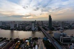 För Bangkok för flyg- sikt som stad för passerande för kors flod är i stadens centrum med härlig himmel efter solnedgång Arkivbild