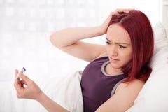 För barn kvinna dåligt med febertermometern Arkivfoto