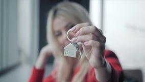 för begreppsdollaren för 100 bills det gjorda huset intecknar ut Kvinnan i röd tangent för innehav för affärsdräkt med huset form arkivfilmer