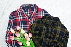 för begreppsframsida för skönhet blå ljus kvinna för makeup för mode Två rutiga skjortor och rosa tulpan Träbaksida Royaltyfria Bilder