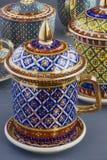För Bencharong för fem färger för thailändsk konst traditionell kopp te över blå oskarp bakgrund royaltyfri bild