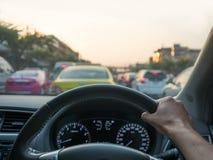 För bil sikt ombord av det hållande styrninghjulet för hand Fotografering för Bildbyråer