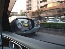 För bil som chaufför ombord utanför ser till sidospegeln Arkivbild