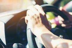 För bilchaufför för selektiv fokus som händer rymmer styrninghjulet arkivfoton
