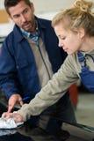 För bilordförande för ung kvinnlig mekaniker polerande hålla ögonen på royaltyfri fotografi