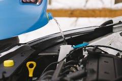 För bilvinter för man hällande vätska för packning för vindruta Royaltyfri Foto