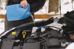 För bilvinter för man hällande vätska för packning för vindruta Arkivfoton