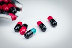 För blått-gräsplan för selektiv fokus preventivpiller kapsel och drogmagasin med densvart kapseln global sjukvård Antibiotikumdro arkivfoto