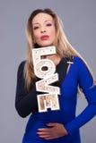 För blåttklänning för kvinna bärande symbol för förälskelse för tecken hållande Royaltyfri Foto