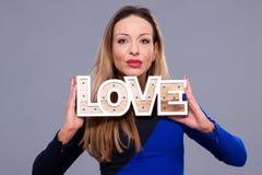 För blåttklänning för kvinna bärande symbol för förälskelse för tecken hållande Arkivfoto