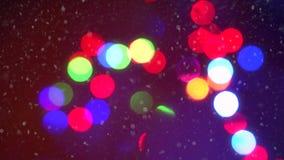 För blinkajul för Closeup som färgrik bakgrund för bokeh för ljus för girland omges av fallande snöflingor lager videofilmer