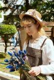 För för bondedräkt och innehav för ung kvinna bärande bukett för vildblommor royaltyfri foto