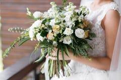 för brudbrudgum för bukett brud- händer Brud`en s Härligt av vita blommor och grönska, dekorerat med det siden- bandet, lögner på Royaltyfri Fotografi