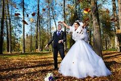 för brudgumiand för brud fallande joyful leaves fotografering för bildbyråer