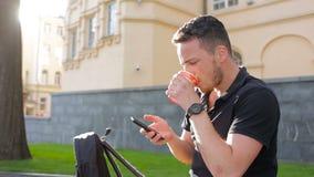 För brukstelefon för ung man ett sammanträde på en bänk som dricker kaffe utanför i stad arkivfilmer