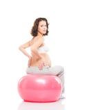 För brunettkvinna för barn gravid utbildning med en konditionboll Arkivbild