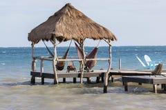 För Caye för paraply för parasoll för stolar för strandGazebovardagsrum Belize Caulker semesterort för karibiskt hav arkivbilder
