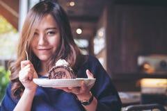 För chokladkakan för den asiatiska kvinnan tycker om hållande rulle och den piskade kräm och gaffeln med mening lyckliga och att  arkivbild