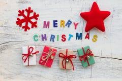 För Chritsmas för ` glade bokstäver `, julgarnering och gåvaaskar på vitt trä Royaltyfria Bilder