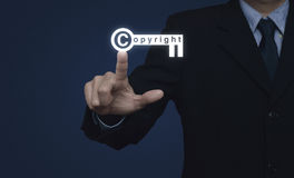 För copyright-tangent för affärsman trängande symbol på blå bakgrund, kopia arkivfoton