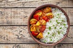 För currychili för feg jalfrezi indiskt kryddigt kött med basmati ris och grönsaker i leramaträtt royaltyfria bilder