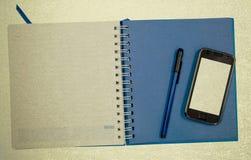 För dagbokbok för mobiltelefon blå bakgrund för tappning Royaltyfri Foto