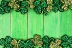För dagdubblett för St Patricks gräns av treklöverer över grönt trä Royaltyfri Fotografi