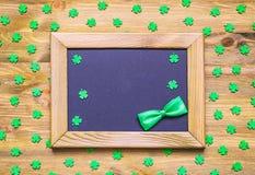 För dagferie för St Patricks bakgrund med gröna quatrefoils och ram med den gröna flugan på träbakgrunden Royaltyfri Fotografi