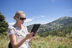 för dator tablet utomhus genom att använda kvinnan Royaltyfri Bild