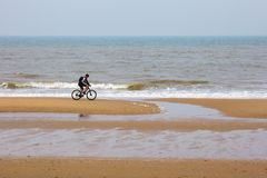 För Den Haag för NordsjönHague Scheveningen nederländska holländska sol män för morgon för reflexion för kust för cyklist för cyk arkivbild