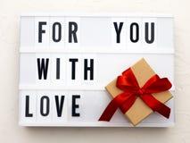FÖR DIG MED FÖRÄLSKELSEord på lightbox på rät maskabakgrund med slågna in gåvaaskar Begrepp för dag för valentin` s royaltyfria bilder