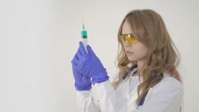 För doktorsinnehav för ung kvinna injektionsspruta på vit bakgrund lager videofilmer